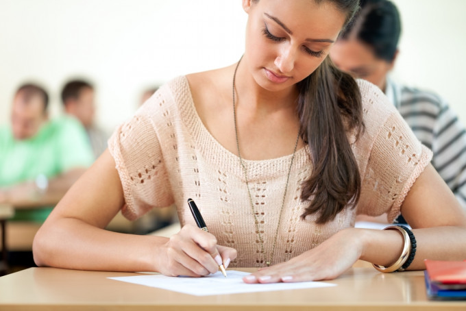 Student girl sitting for exam in a classroom