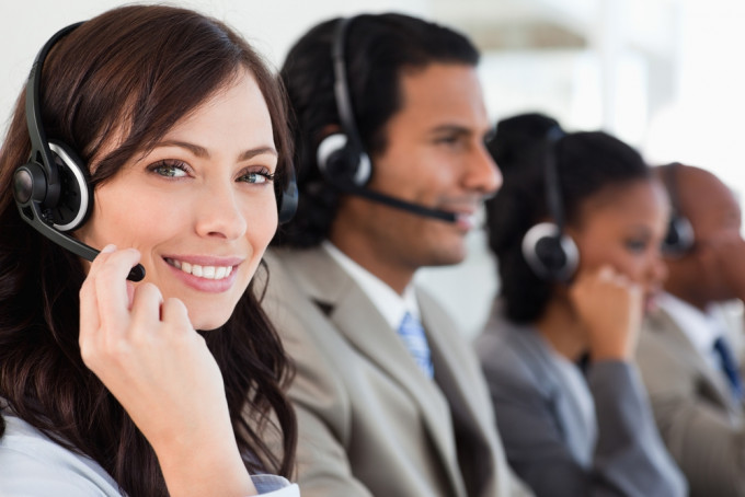 Smiling worker doing her job with a headset while looking at the camera