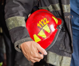 Midsection of male firefighter holding red helmet at fire station