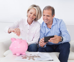 Happy Mature Couple Calculating Coin In The Piggybank