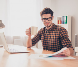 Smart successful businessman doing paperwork while drinking coffee