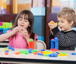 Little children playing with blocks in classroom